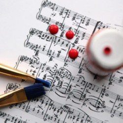 Sheet music with paintbrushes on top
