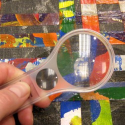 magnifying glass over colored paper