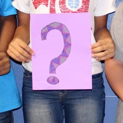 three students holding question signs
