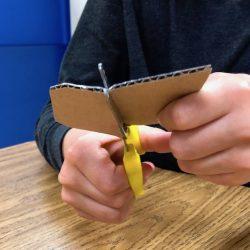 student cutting cardboard