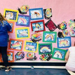 Image of volunteers hanging up artwork