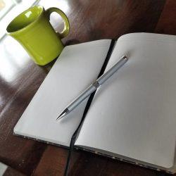 Notebook, pen and coffee mug