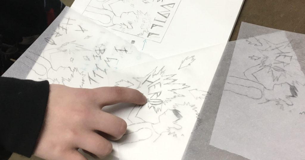 Student pointing at a drawing in a sketchbook