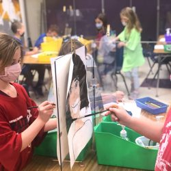 students using plexiglass dividers as easels to paint portraits