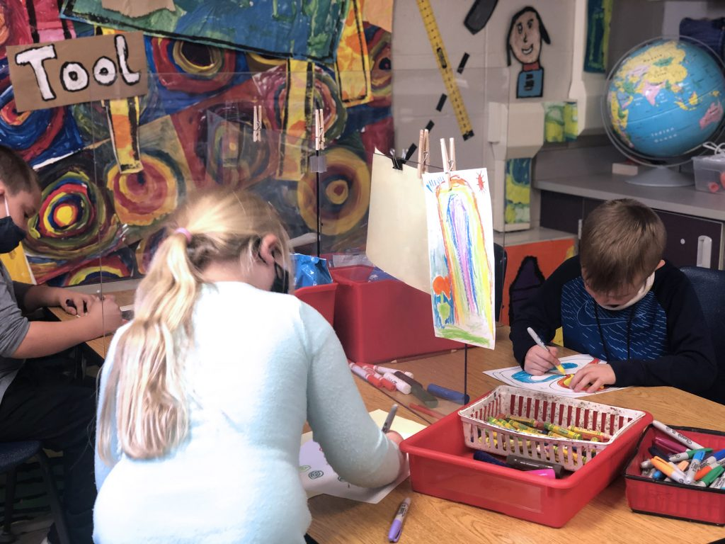 two students drawing with artwork clipped to plexiglass barriers