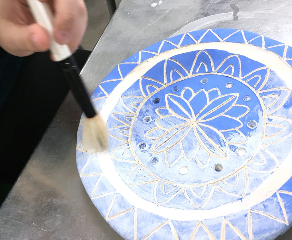 student glazing a radial floral design