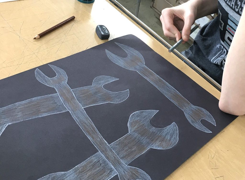 student drawing wrenches with colored pencil on black paper