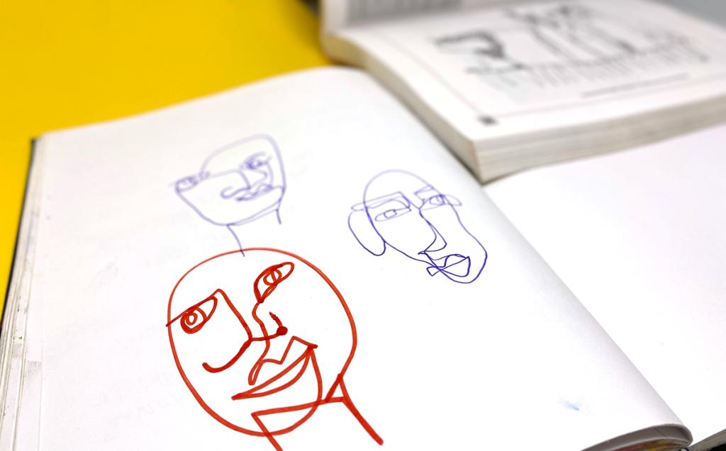 blind contour portraits in sketchbook