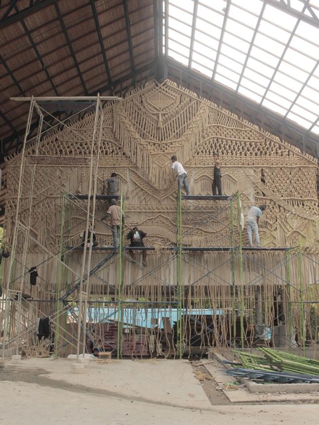artisans installing fiber mural