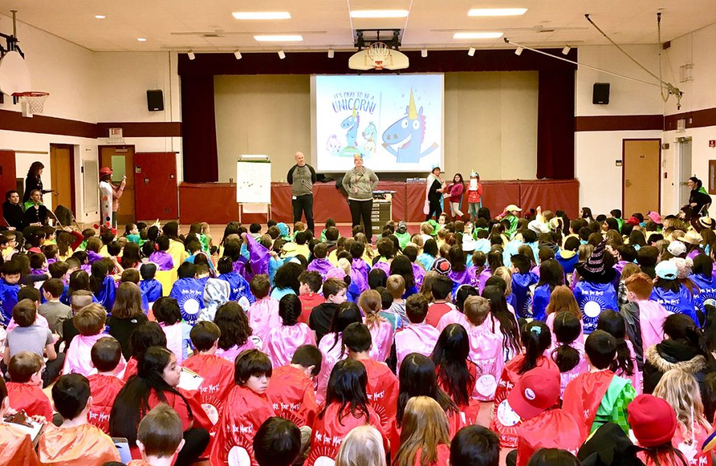 """jason tharp presenting """"it's okay to be a unicorn"""" book to students"""