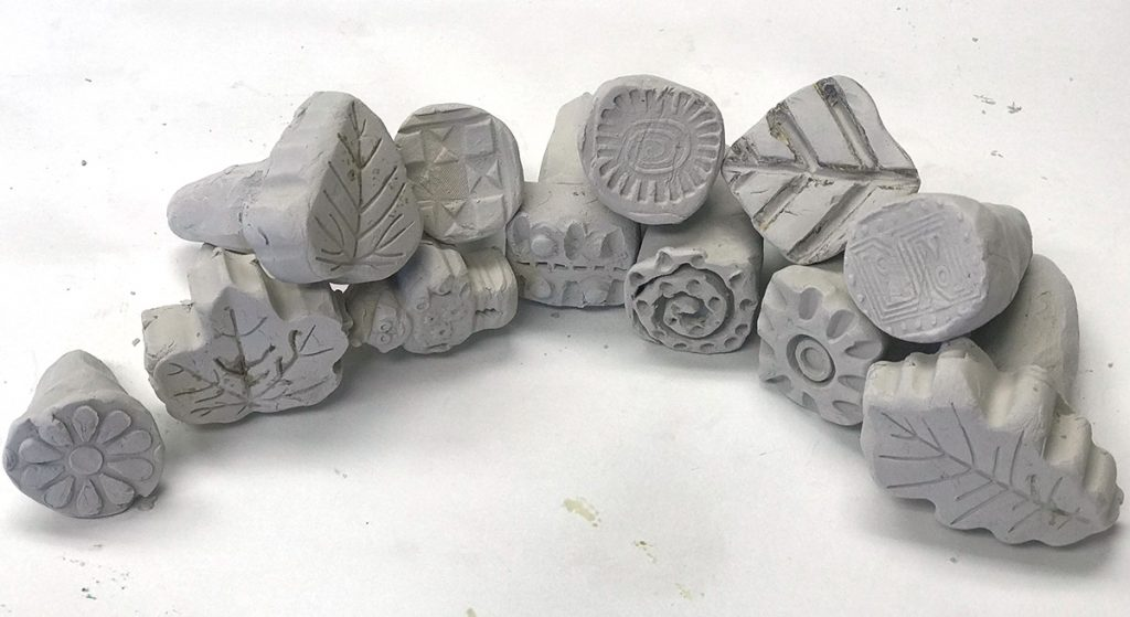 curved row of hand carved texture stamps out of clay