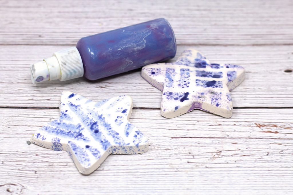 two white ceramic stars with blue spray and small spray bottle