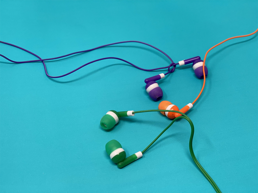 three colored earbuds headphones on teal background