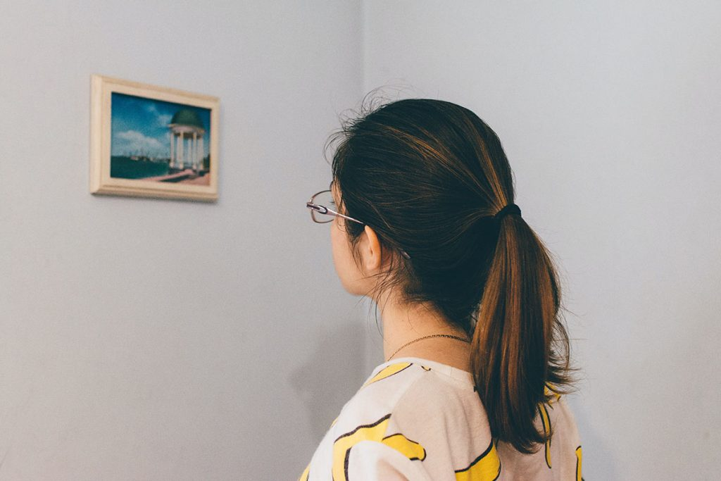 girl looking at small painting on wall