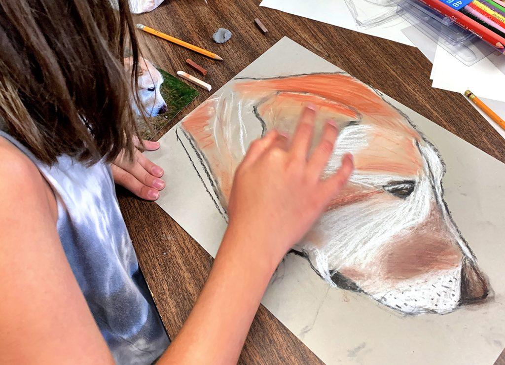 girl blending pastels dog drawing