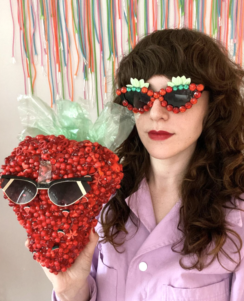 woman holding strawberry made of beads