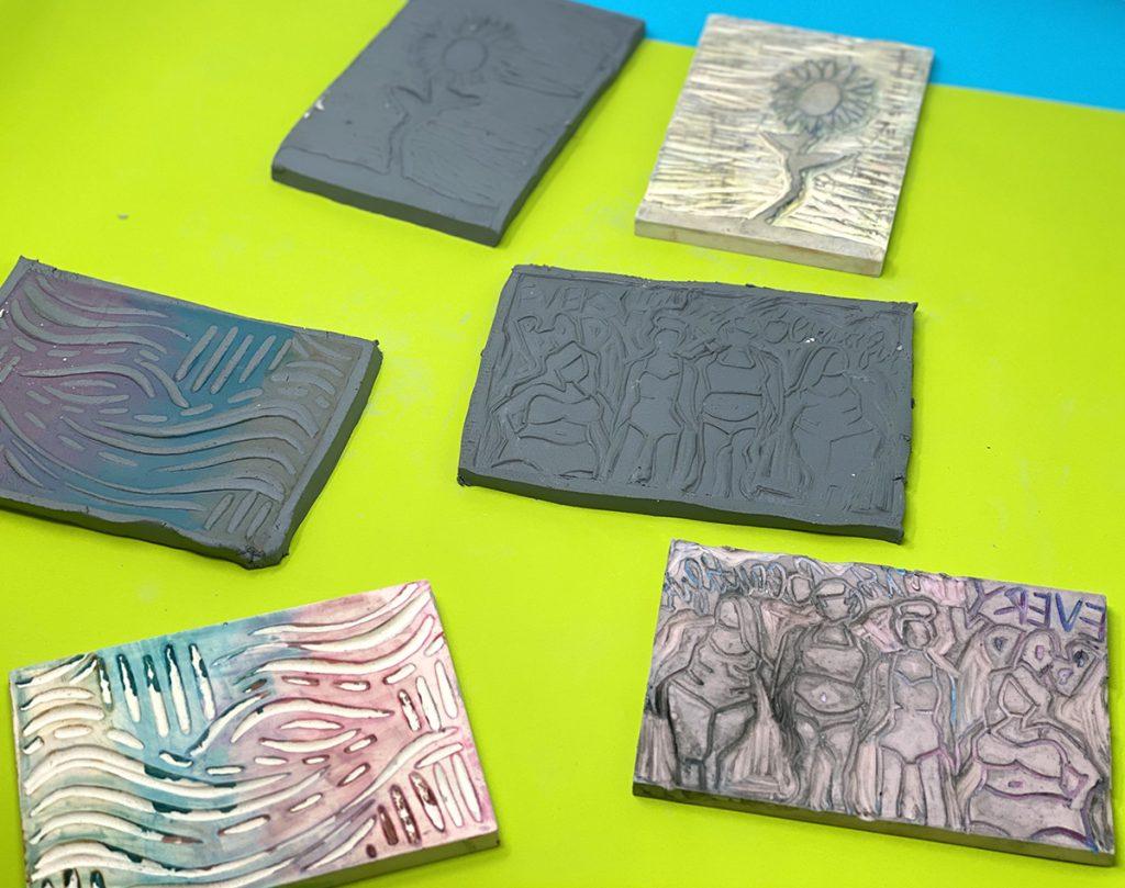 three carved linoleum blocks, three clay slabs