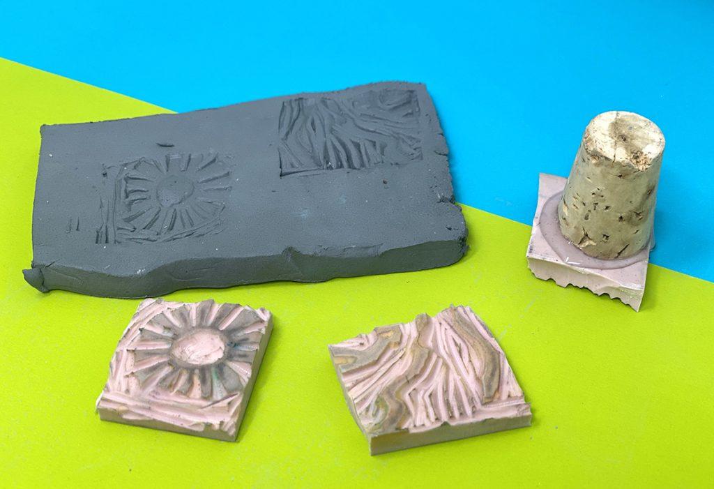 three cut linoleum blocks, cork handle, clay slab