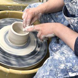 hands throwing pot on wheel