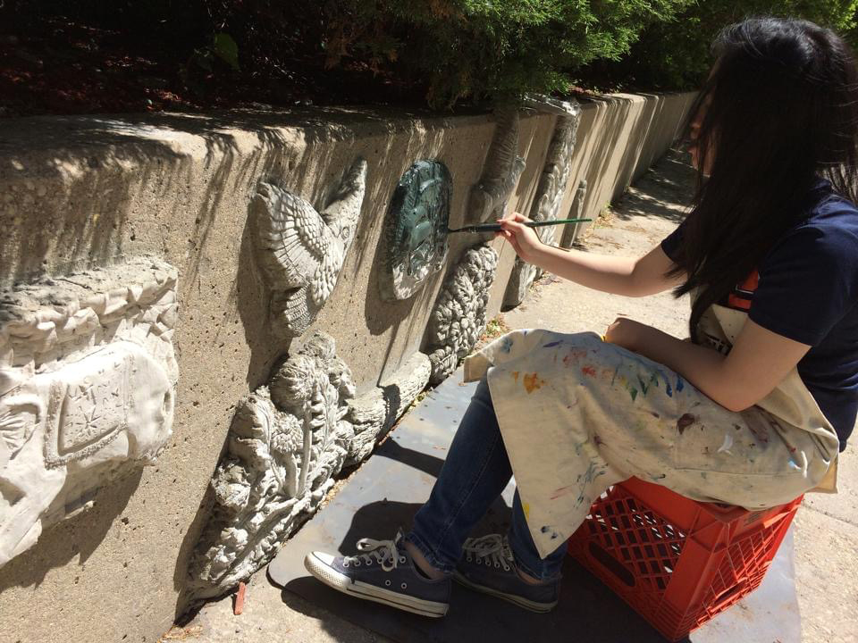 student painting concrete wall relief