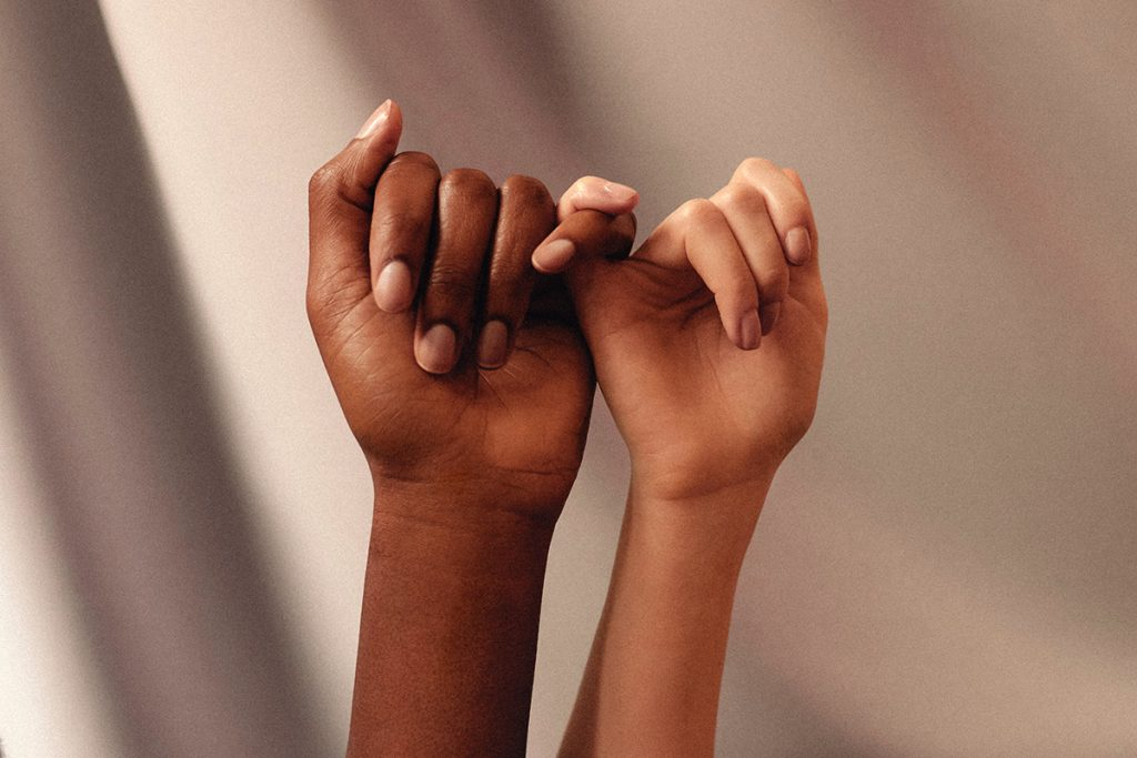 two hands with different skin colors pinkies linked