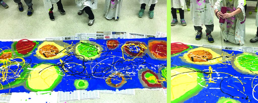 students squeezing paint on large paper on floor