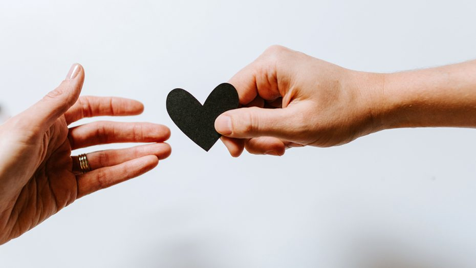 two hands exchanging black paper heart