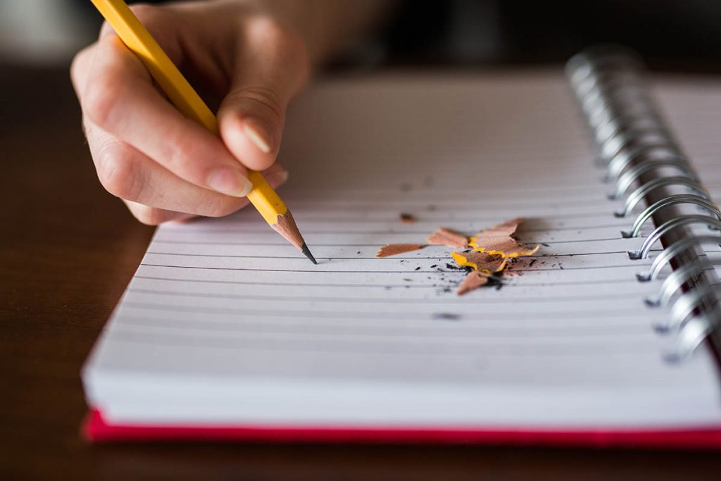 hand holding pencil open notebook